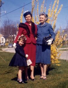 Mom, Nana and I with Easter hats, by the forsythia, in 1961